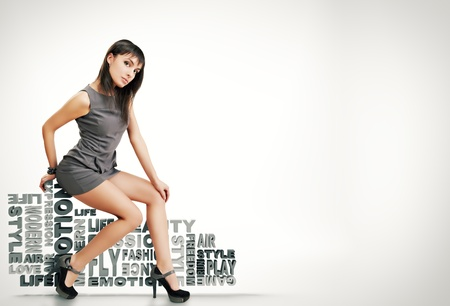 cover girls: beautiful girl sits on words on a white background. fashion theme  Stock Photo