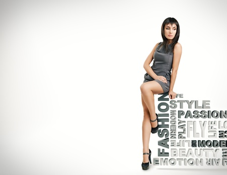 fashion  woman: beautiful girl sits on words on a white background. fashion theme  Stock Photo
