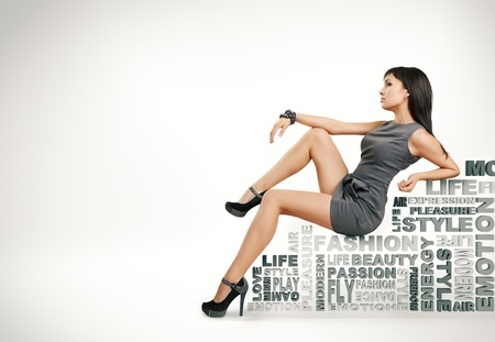 moda ropa: hermosa chica se sienta en palabras sobre un fondo blanco. moda tema