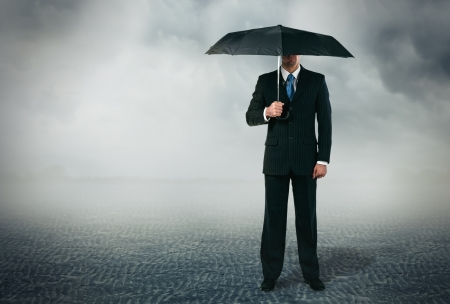 Businessman with umbrella standing at cloudy background photo