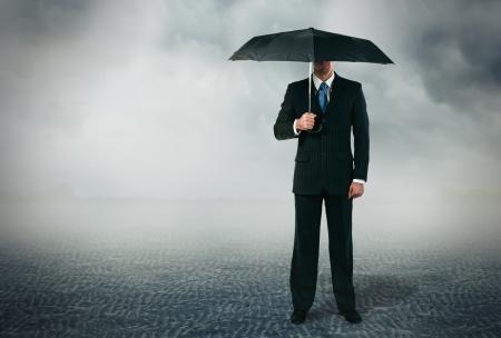 lluvia paraguas: Hombre de negocios con paraguas de pie en el fondo nublado