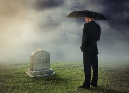 Businessman with umbrella standing near tomb of crisis photo