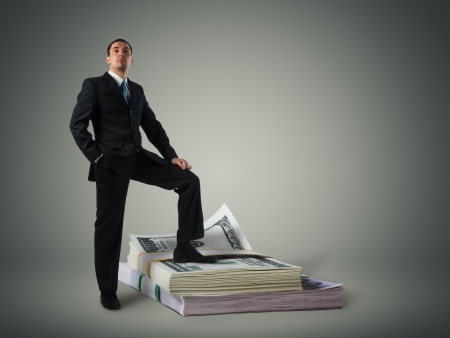 Businessman standing on a stack of dollars Stock Photo - 16465270