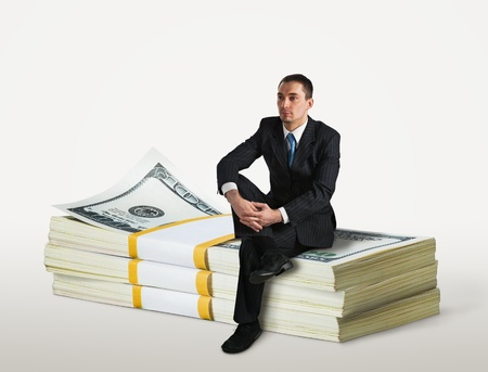 american banker: Businessman sitting on a stack of dollars