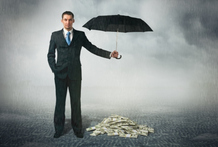 seguridad laboral: Hombre de negocios con el paraguas se sit�a en el fondo nublado y protege un dinero de la seguridad financiera