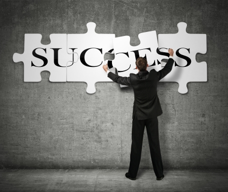 Businessman making a puzzle on the wall with the word Success photo