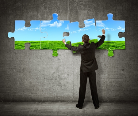 green wall: Businessman making a puzzle on the wall with  picture of nature Stock Photo