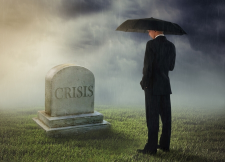 Businessman with umbrella standing near tomb of crisis Stock Photo - 16469927