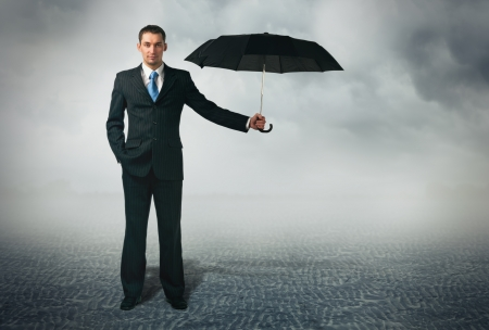 Businessman with umbrella standing at cloudy background Stock Photo - 16469921