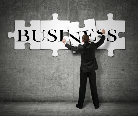 puzzle business: Businessman making a puzzle on the wall with the word Business
