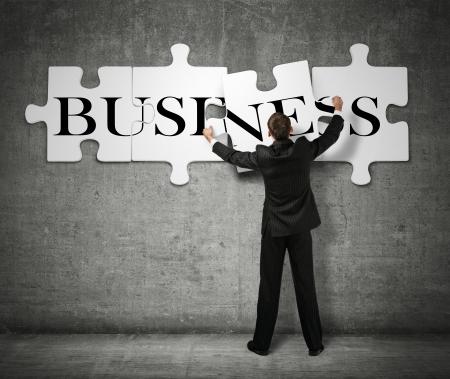 entreprise puzzle: Homme d'affaires faisant un puzzle sur le mur avec le mot d'affaires