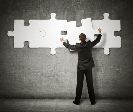 toma de decision: De negocios que hace un rompecabezas en la pared Foto de archivo