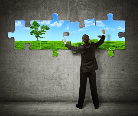puzzles: Businessman making a puzzle on the wall with  picture of nature Stock Photo