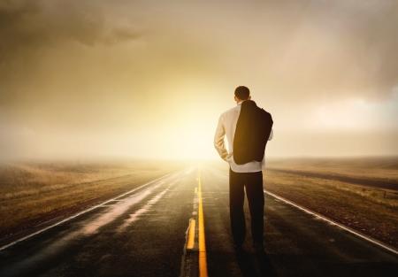 walking alone: Empresario caminando en la carretera