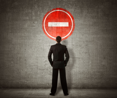 with stop sign: Businessman standing in front of no entry sign Stock Photo