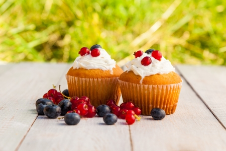 Cakes with cream and berries on wooden boards