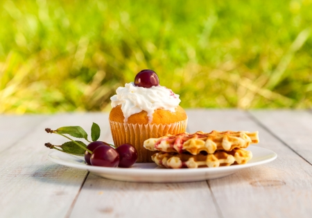 Cakes with cherry on a white plate on wooden boards photo