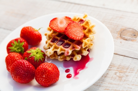 Strawberries and wafer on a white plate photo