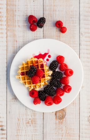 Blackberry and raspberry with a waffle on a white plate photo