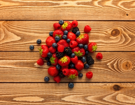 berries: Berries on Wooden Background. Stock Photo