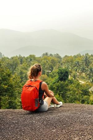 mujer mirando el horizonte: Turista de la mujer que se sienta en la cima de una montaña