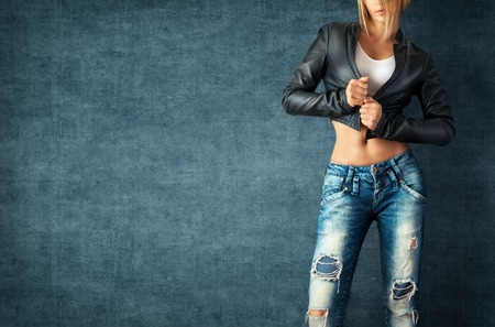 Sexy jonge vrouw in een trendy kleren op een grunge achtergrond