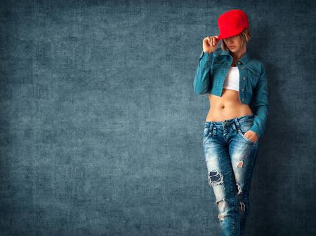 mezclilla: Sexy mujer joven en una ropa de moda sobre un fondo grunge