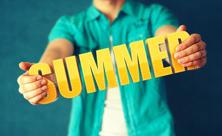 Man holds word Summer on bright colorful background photo