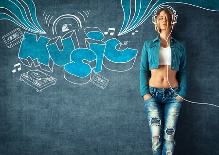 Sexy young woman in a trendy clothes on a grunge background. Musical background