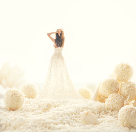 nude bride: Woman in white dress in a fairy world of big candies. Unusual modern art Stock Photo