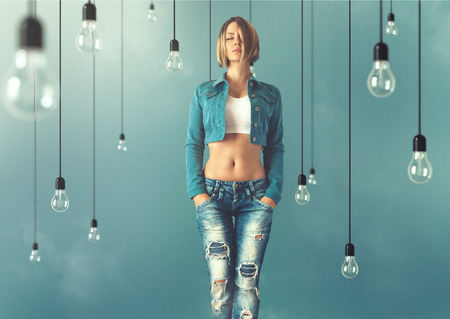 Young woman in a trendy clothes stand between lightbulbs. Unusual art image photo