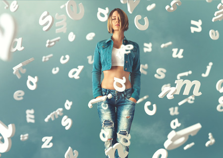 Sexy young woman in a trendy clothes with letters flying arround her photo