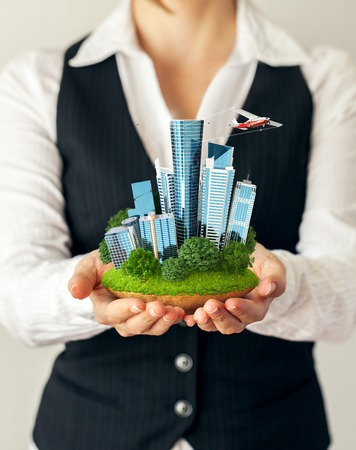 dream house: Small fantastic island with a modern city in womens hands. Stock Photo