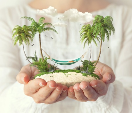 fantastic world: Small fantastic island with a hammock and palms in womens hands.