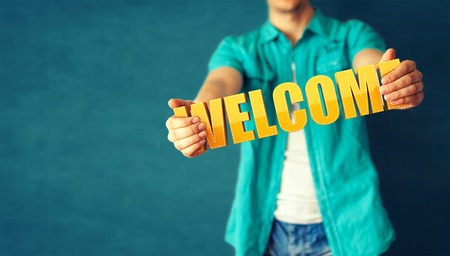Man holds word welcome on bright colorful background photo