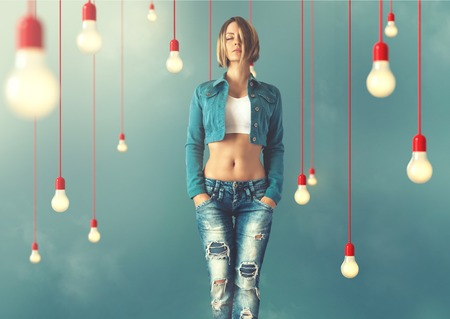 thin bulb: Young woman in a trendy clothes stand between lightbulbs  Unusual art image