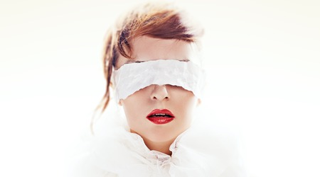 Portrait of attractive woman blindfolded with white paper ribbon photo