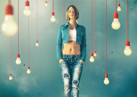 Young woman in a trendy clothes stand between lightbulbs  Unusual art image