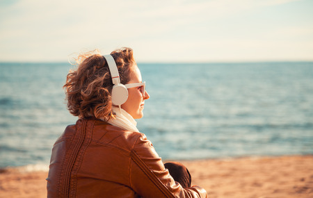 Young woman in a headphones at the beach photo