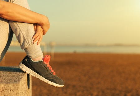 Sitting Womans feet in a sneakers. Stock Photo