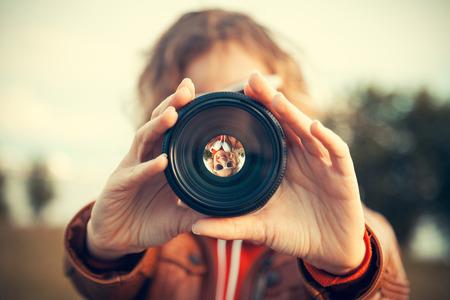 objetivo: Mujer joven que mira a través de la lente de la cámara Foto de archivo