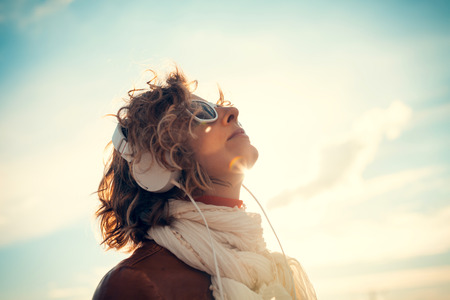 Young woman in a headphones at against the sky Stock Photo - 29425297