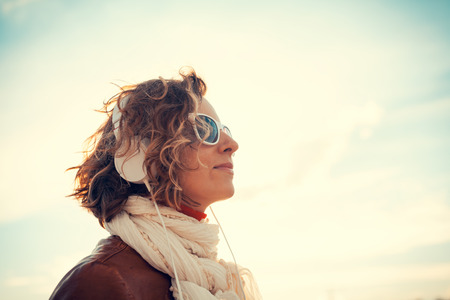 Young woman in a headphones at against the sky Stock Photo - 29425299