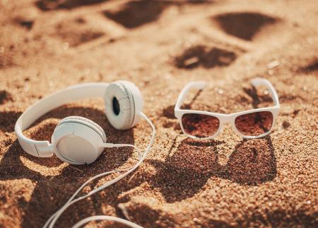 White sunglasses and headphones on sand