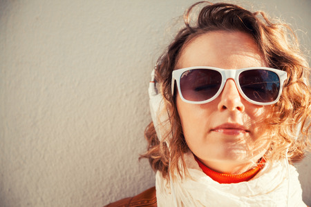 Beautiful young woman in a sunglasses and headphones listening music near the wall Stock Photo - 29425302