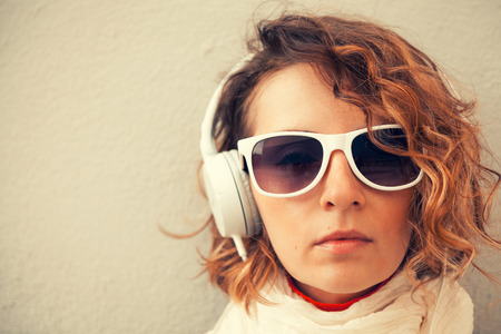Beautiful young woman in a sunglasses and headphones listening music near the wall Stock Photo - 29425304