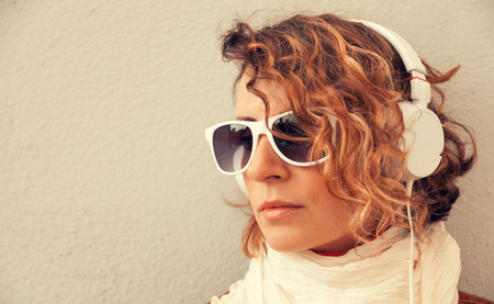 Beautiful young woman in a sunglasses and headphones listening music near the wall Stock Photo - 29425322