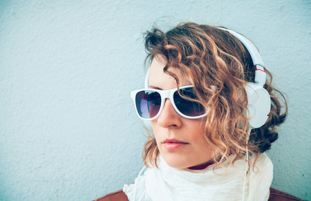 Beautiful young woman in a sunglasses and headphones listening music near the wall photo