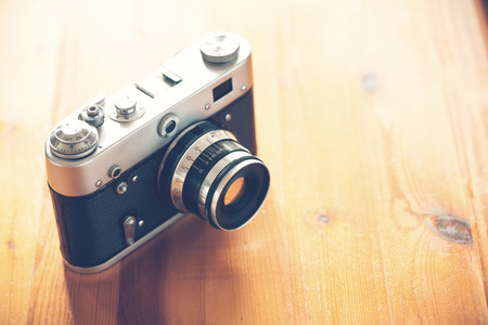 Old vintage camera on a wooden table. photo