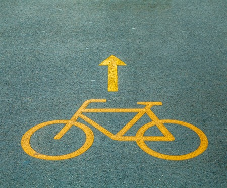 bicycle lane: Yellow Bicycle path sign on the asphalt road